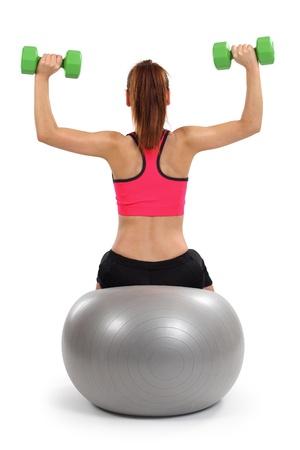 ein Weibchen von hinten tun Kurzhantel Schulterdrücken im Sitzen auf einem Gymnastikball. Standard-Bild