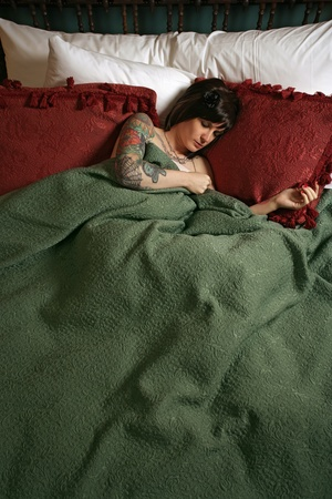 a beautiful female with tattoos, sleeping alone in a large bed. photo