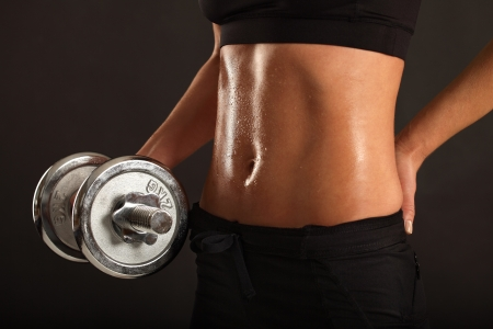 Image of the stomach from a sweaty slim female lifting a dumbbell.