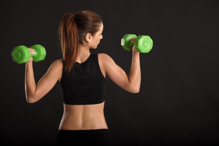 a toned young female exercising with dumbbells. photo