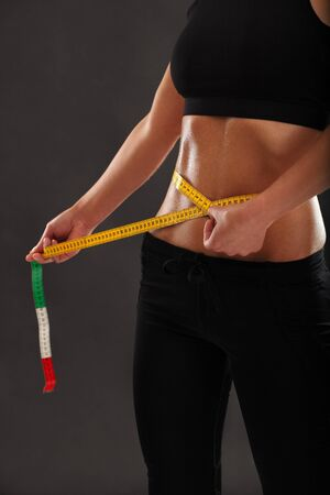 a tanned slim young woman measuring her sweaty waistline over dark background. Stock Photo - 14486782