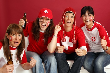 Photo of female Swiss sports fans smiling and cheering for their team. photo