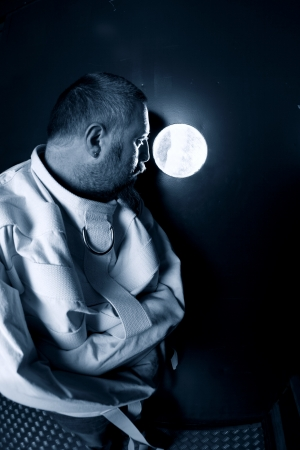 asylum: Photo of an insane man in his forties wearing a straitjacket standing in a cell of an asylum with the light from the hallway streaming in. Stock Photo