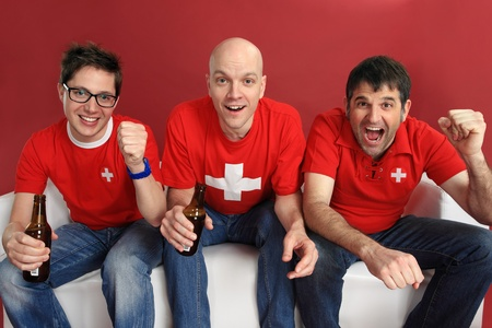 three male Swiss sports fans cheering for their team. photo