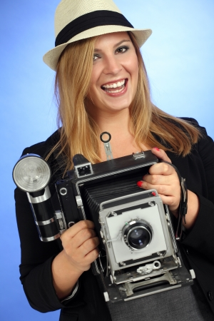 Photo of a beautiful young blond woman holding a vintage 4x6 film camera. photo