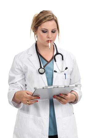 persona fumando: Foto de un médico rubio que fuma un cigarrillo mientras miraba una carta médica.