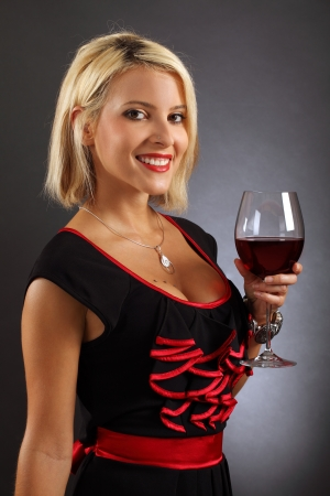 Photo of a sexy blond female holding a large glass of red wine. photo