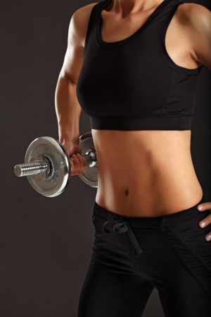 Photo of a toned young female exercising with dumbbells. Stock Photo - 14719160