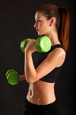 Photo of a slim female lifting dumbbells doing bicep curls over black background. Stock Photo - 14719161