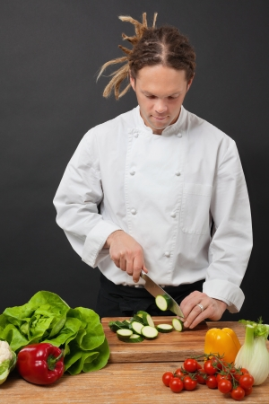 cutting: a chef chopping vegetables on a wooden cutting board  Stock Photo