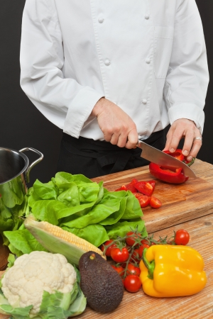 chopping: a chef chopping vegetables on a wooden cutting board  Stock Photo