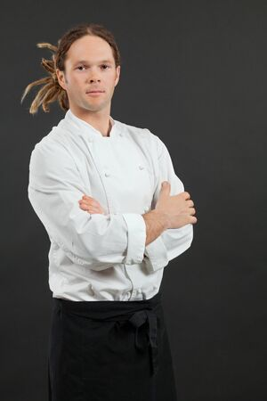a male chef with dreadlocks, standing with his arms crossed over dark background  photo