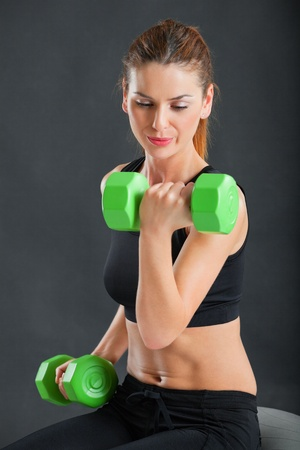 curls: an attractive female doing dumbbell curls while sitting on an exercise ball  Stock Photo