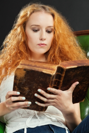 a female with red curly hair reading an old book  photo