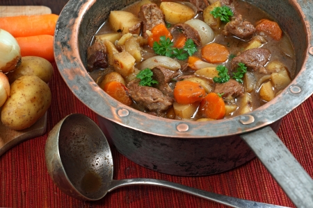 ladles: Photo of of Irish Stew or Guinness Stew made in an old well worn copper pot.