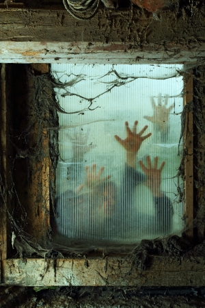 Photo of zombies outside a window that is covered with spiderwebs and filth. Banque d'images