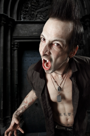 a male vampire with mouth open and fangs showing.  Harsh lighting and heavily filtered for scarier feel. photo