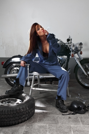 a beautiful female mechanic working on a motorcycle wearing overalls, holding a large ratchet and smoking a cigarette. photo