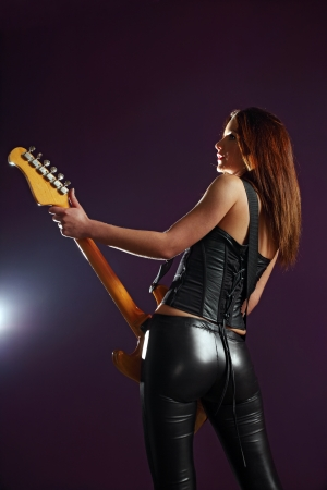 of the back of a female playing an electric guitar with a spotlight on her front.