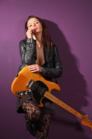 a female guitarist wearing a leather jacket and leaning up against a purple wall. photo