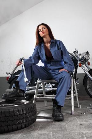 overol: Foto de una hermosa hembra mec�nico trabajando en una motocicleta vestido con un mono y la celebraci�n de un trinquete grande.