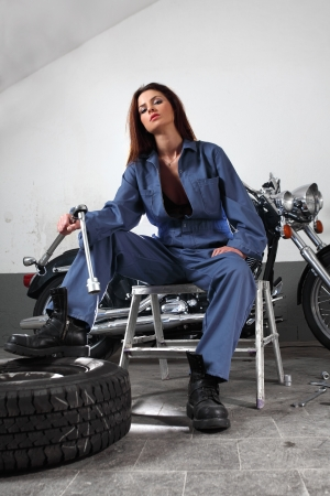 garage: Photo of a beautiful female mechanic working on a motorcycle wearing overalls and holding a large ratchet.