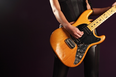 sexy guitar: the body of a female guitar player standing and playing over a dark background.