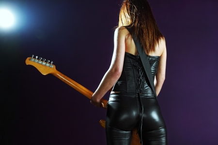 the back of a female guitar player standing and playing in front of a spotlight.