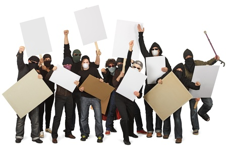 protester: Photo of a group of unrecognizable protesters wearing masks and holdings signs.