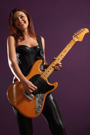 Photo of the back of a female guitar player standing and playing in front of a spotlight. photo
