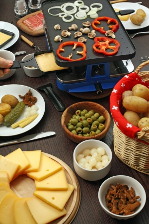 Photo of a table full of items for a traditional Raclette dinner, including slices of cheese, white onions, potatoes, olives, mushrooms, and the grill with the utensils. photo