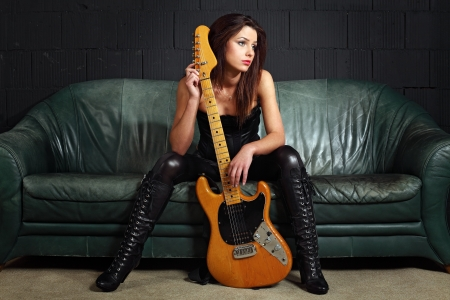 Photo of a sexy female guitar player wearing leather boots and sitting on old leather couch. Imagens