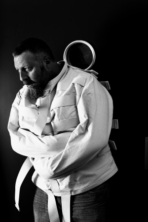 madman: Photo of a insane man in his forties wearing a straitjacket leaning up against an asylum door.