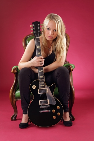 sexy guitar: Photo of a gorgeous blond sitting in a leather chair holding a black electric guitar. Stock Photo