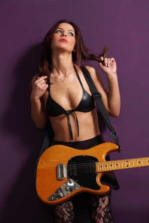 electric guitar: Photo of a female guitarist leaning up against a purple wall.