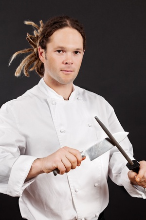 young knife: Photo of a chef with dreadlocks sharpening his chopping knife. Stock Photo