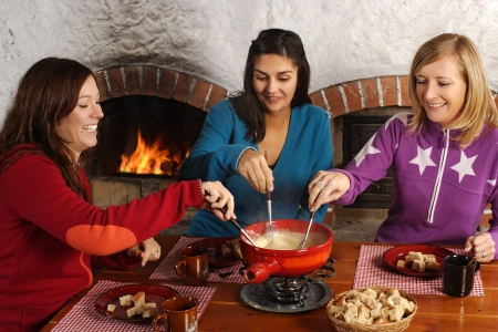 Photo of three beautiful females dipping bread into the melted cheese in a fondue pot. Stock Photo