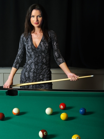 Photo of a beautiful brunette holding a pool cue and playing pool. photo