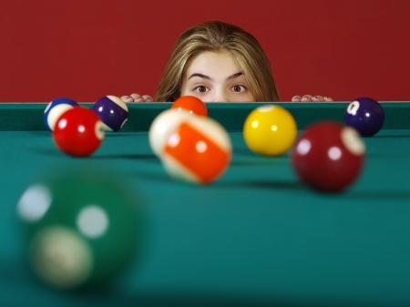 Photo d'une jeune fille vérifier les boules de billard pour une chance à un bon coup.