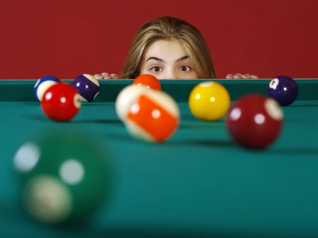 pool table: Photo of a young girl checking the billiard balls for a chance at a good shot.