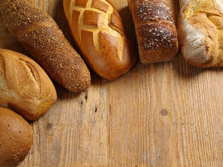 uncut: Loaves of uncut bread resting on an old wood table. Stock Photo