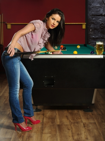 Beautiful brunette holding a pool cue and playing pool. photo