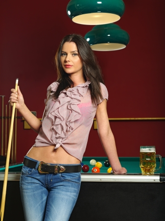 a beautiful brunette holding a pool cue and leaning against a pool table. Stock Photo