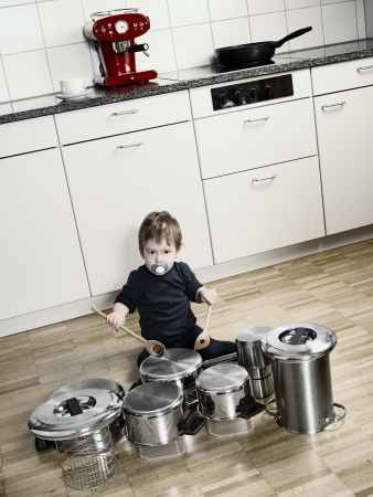 increased:  an adorable young boy using wooden spoons to bang pots and pans that are set up like a drum set. Desaturated and contrast increased.
