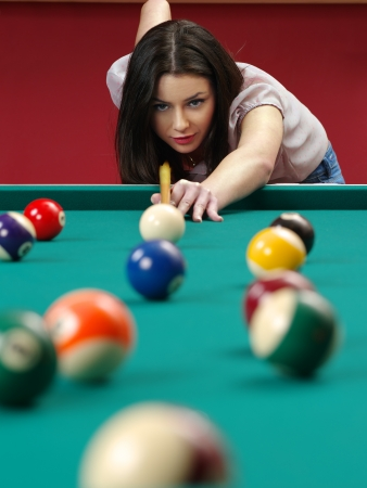 Photo of a beautiful brunette about to shoot pool.
