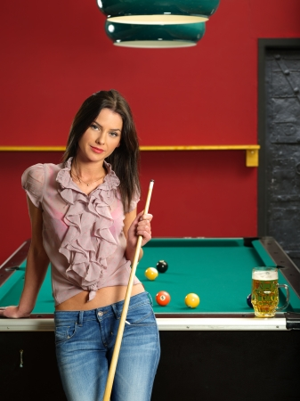 Photo of a beautiful brunette holding a pool cue and leaning against a pool table.