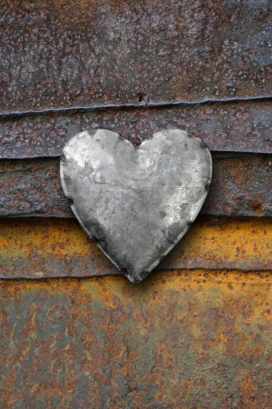 Photo of metal heart on a rusting iron background. photo