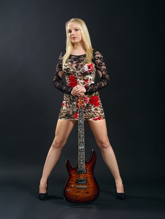 Photo of a sexy blond female standing and holding an electric guitar over a black background. photo