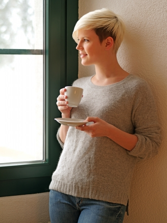 Photo of a beautiful young female drinking from a cup and looking out the window during winter. Stock Photo