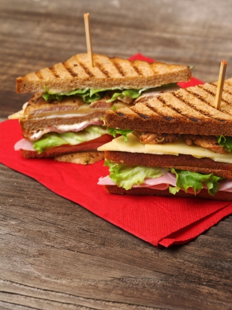 Photo of a club sandwich made with turkey, bacon, ham, tomato, cheese, lettuce on a red napkin and old wood picnic table.